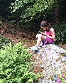 Isabel writing on a rock at The Poetry Studio